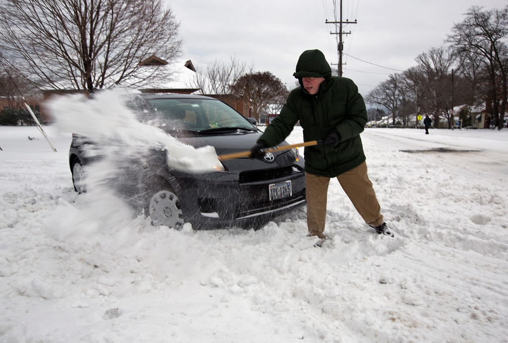 Description of . Butch Inman, of Norfolk,, Va., who works for the City of Norfolk, digs his car out of the snow Wednesday morning, Jan. 29, 2014. The coast of Virginia was blanketed in up to 10 inches of snow Wednesday, with many workers in the heavily populated Hampton Roads region being told to stay home rather than travel to work in dangerous conditions. (AP Photo/The Virginian-Pilot, The' N. Pham)