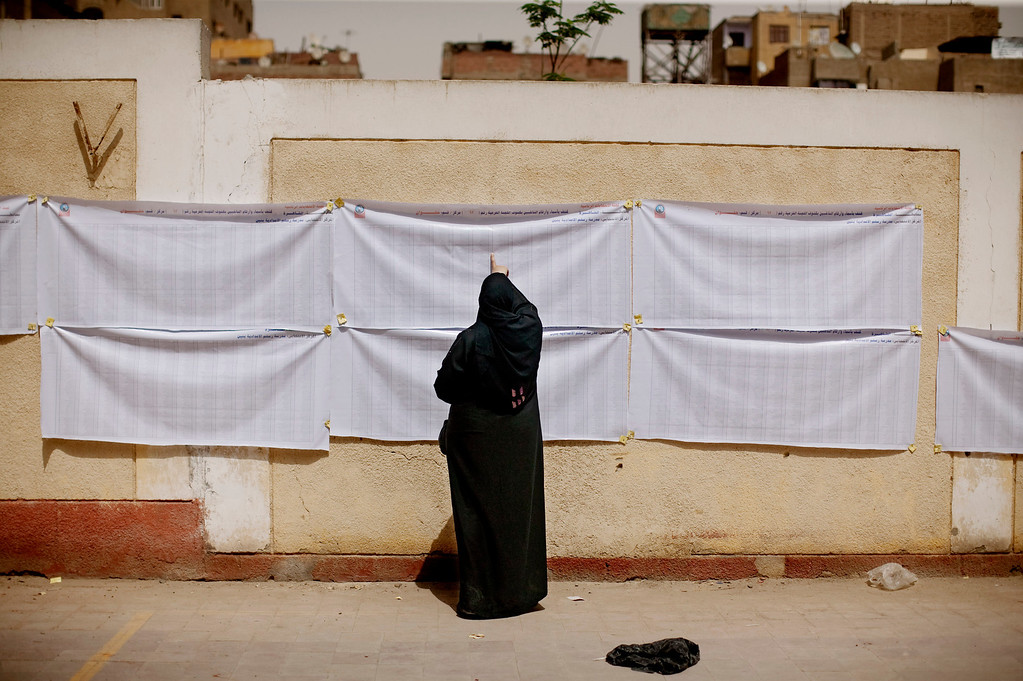 Description of . In this May 23, 2012 file photo, an Egyptian woman searches for her name on a registration list outside a polling station in Helwan, a southern suburb of Cario, Egypt.  Egypt commenced two days of presidential voting after 16 months of interim rule by the Supreme Council of Armed Forces. This election was the first free and fair presidential race since the ouster of former President Hosni Mubarak.  (AP Photo/Pete Muller, File)