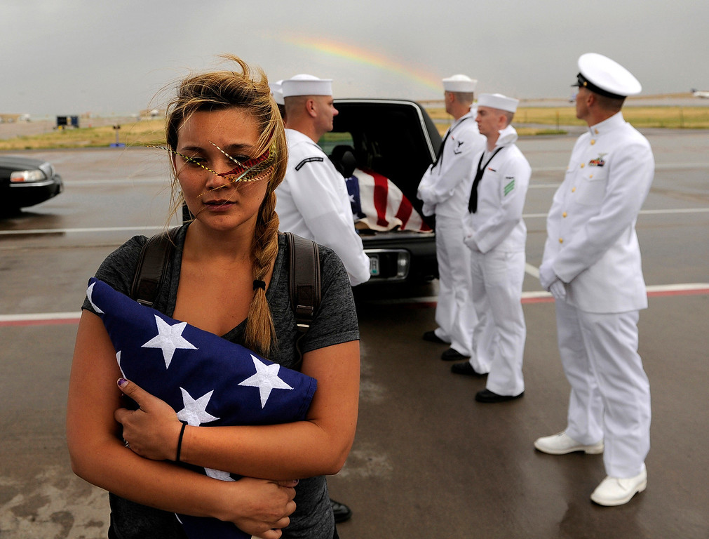 Description of . Chantel Blunk, wife of Jonathan Blunk, waits on the tarmac at Denver International Airport as her husband's body is prepared to be flown to Reno, Nevada for his full military funeral. Blunk, a five-year U.S. Navy veteran, was killed when James Holmes opened fire at a crowded movie theater. RJ Sangosti, The Denver Post