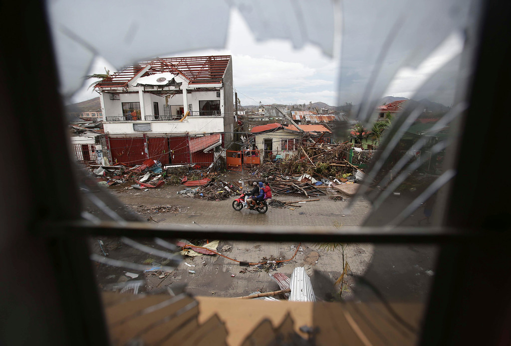 Description of . Damaged homes are seen through a broken window after strong winds from Typhoon Haiyan tore down houses at Tacloban city, Leyte province, central Philippines on Tuesday, Nov. 12, 2013. Four days after Typhoon Haiyan struck the eastern Philippines, assistance is only just beginning to arrive. (AP Photo/Aaron Favila)