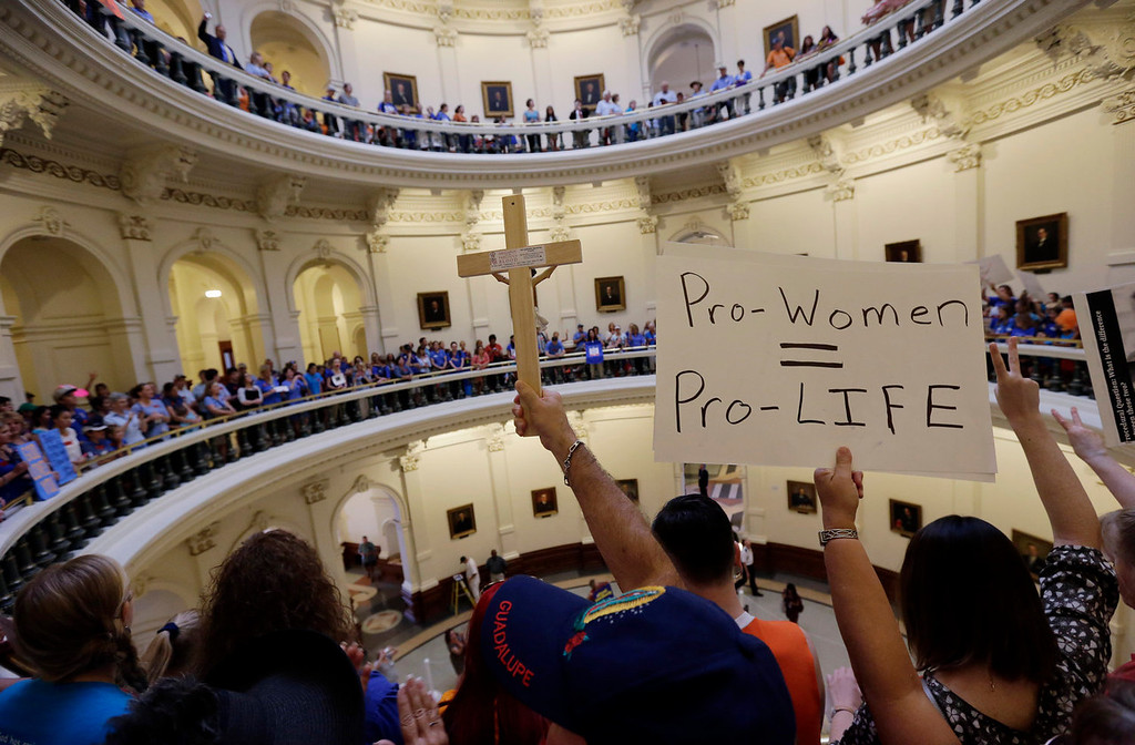 Description of . Anti-abortion supporters and pro-abortion rights supporters crowd into the rotunda of the Texas capitol, Monday, July 1, 2013, in Austin, Texas. The Texas Senate has convened for a new 30-day special session to take up a contentious abortion restrictions bill and other issues. (AP Photo/Eric Gay)
