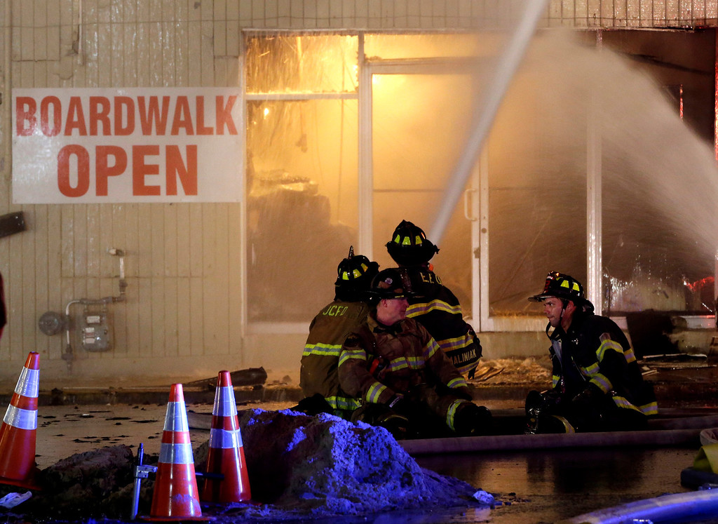 Description of . Firefighters sit on a hose while battling a blaze in a building on the Seaside Park boardwalk on Thursday, Sept. 12, 2013, in Seaside Park, N.J. The fire began in a frozen custard stand on the Seaside Park section of the boardwalk and quickly spread north into neighboring Seaside Heights. (AP Photo/Julio Cortez)