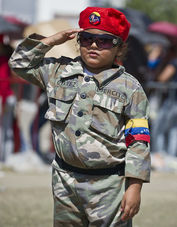 Description of . A little girl wearing a battledress salutes outside of late Venezuelan President Hugo Chavez funeral in Caracas, on March 8, 2013. AFP PHOTO/Ronaldo  Schemidt/AFP/Getty Images