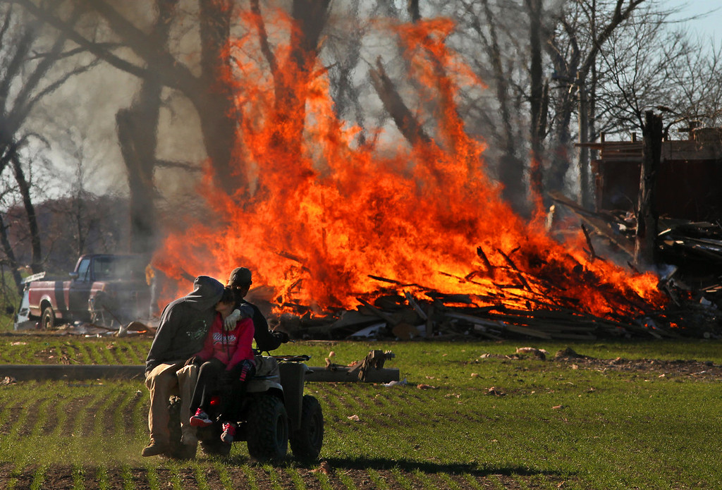 Description of . New Minden, Ill.,  residents burn storm debris from a home destroyed in Sunday's tornado on Monday, Nov. 18, 2013.  Dozens of tornadoes and intense thunderstorms swept across the U.S. Midwest on Sunday, unleashing powerful winds that flattened entire neighborhoods, flipped over cars and uprooted trees. (AP Photo/St. Louis Post-Dispatch, Robert Cohen)