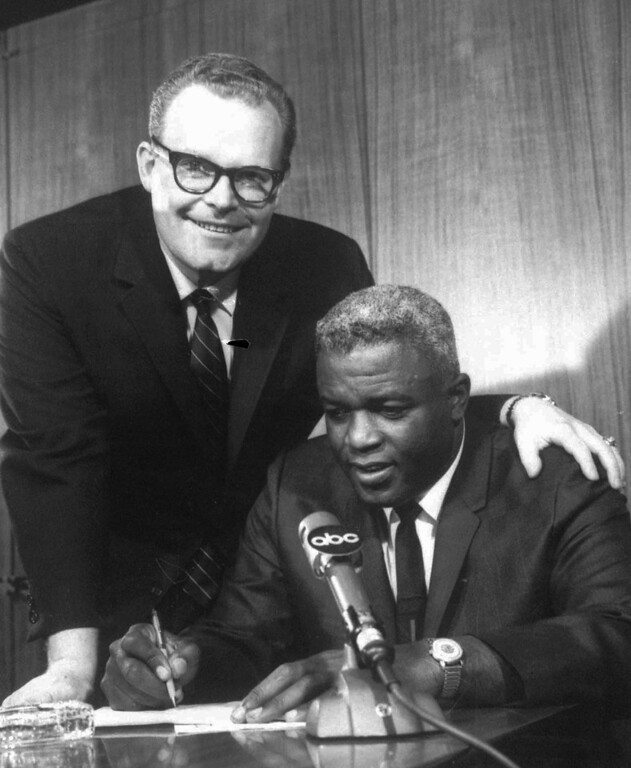 "Description of . Roone Arledge,left,  Vice-President and executive producer of ABC Sports, looks on as baseball legend Jackie Robinson signs on as a commentator analyst for the ABC-TV telecasts of ""Major League Championship Baseball\"" in this March 18, 1965 photo in New York.(AP PHOTO)"