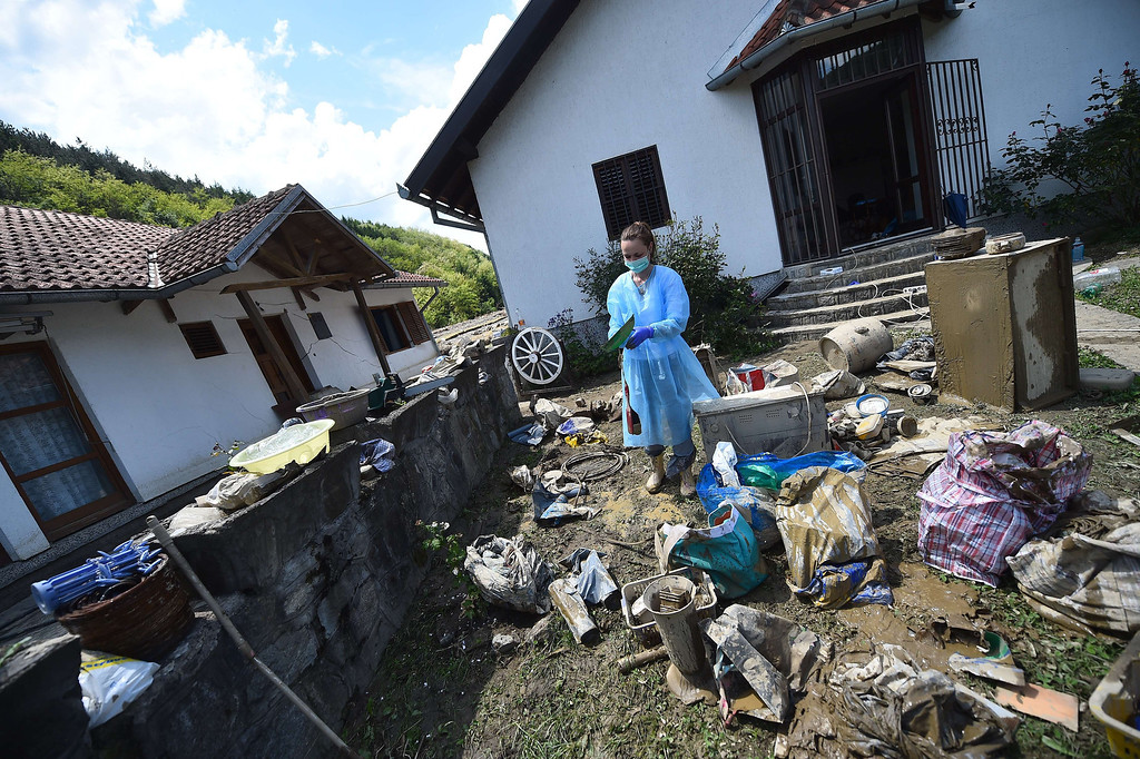 Description of . A woman wearing protective gear sorts personal belongings outside her flooded house in Krupanj, some 130 kilometres south west of Belgrade, on May 20, 2014, after the western Serbian town was hit with floods and landslides, cutting it off for four days. Serbia declared three days of national mourning on May 20 as the death toll from the worst flood to hit the Balkans in living memory rose and health officials warned of a possible epidemic.   AFP PHOTO / ANDREJ ISAKOVIC/AFP/Getty Images