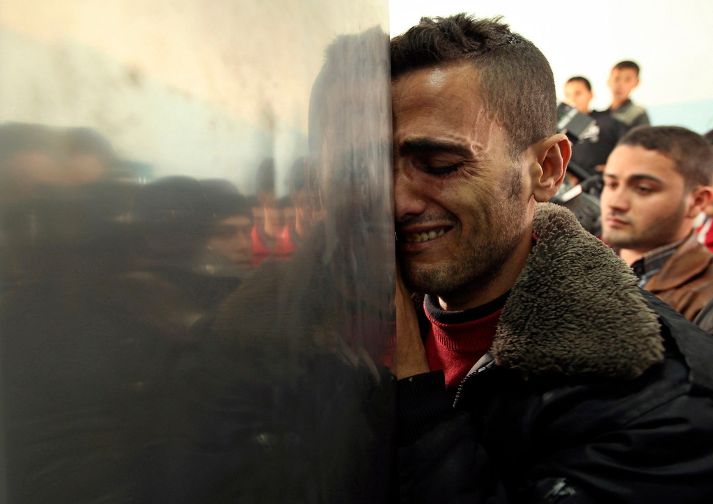 Description of . A Palestinian man reacts upon the arrival of the body of a man, killed by an Israeli strike, at a hospital in Beit Hanoun in the northern Gaza Strip January 18, 2012. An Israeli aircraft and tank strike killed at least one Palestinian close to the border fence in the Hamas-controlled Gaza Strip on Wednesday, medics said.   REUTERS/Mohammed Salem