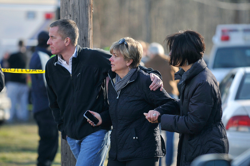 Description of . Parents arrive at the scene of a shooting incident at Sandy Hook Elementary School in Newtown, Connecticut, in this December 14, 2012 handout photo. Twenty-six people, including 20 children, have been killed in a shooting at Sandy Hook Elementary School in Newtown, Connecticut.  REUTERS/John Woike/Hartford Courant/Handout