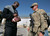 Denver Broncos cornerback Champ Bailey autographs a football for a soldier stationed in the Middle East during a stop on his week-long USO/NFL tour March 17, 2013.   USO Photo by Fred Greaves