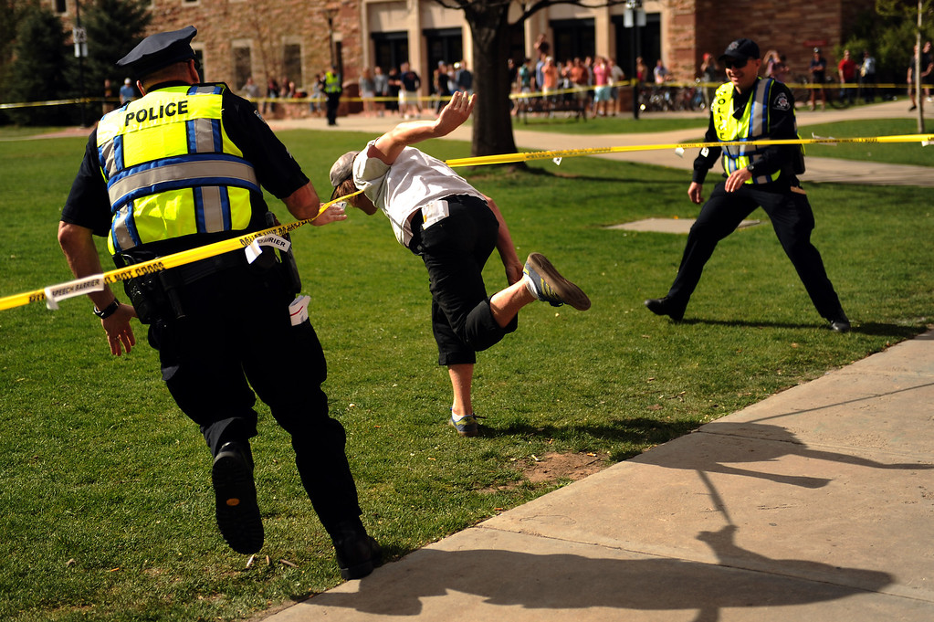 Description of . Officers chase Nathan Ryan, 20, as he makes a break for the closed Norlin Quad on the University of Colorado Boulder campus. The quad was roped off to prevent pro-marijuana protesters from smoking at the school in Boulder, Colorado on Friday, April 20, 2012. Joe Amon, The Denver Post