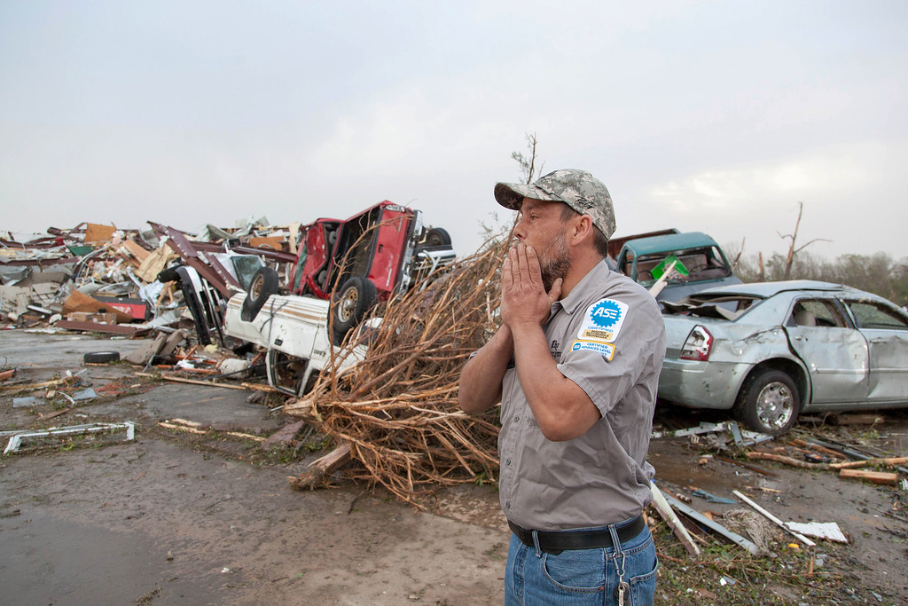 Description of . John Smith reacts after seeing what's left of his auto repair shop in Mayflower, Ark., Monday, April 28, 2014, after a tornado struck the town late Sunday. Mayflower was hit hard Sunday after a tornado system ripped through several states in the central U.S. and left more than a dozen dead in a violent start to this year's storm season, officials said.  (AP Photo/Karen E. Segrave)