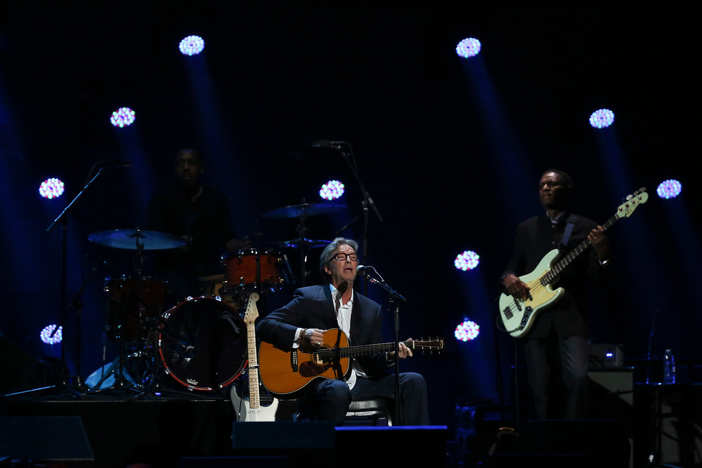 Description of . Eric Clapton plays acoustic guitar during his set at the 12-12-12 benefit concert for victims of Hurricane Sandy, at Madison Square Garden in New York, Dec. 12, 2012. The concert features a lineup of artists spanning five decades. (Damon Winter/The New York Times)