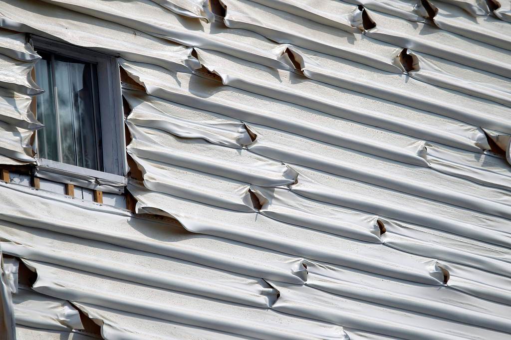 Description of . Melted siding on a home is seen near the scene of a train derailment in Lac Megantic, Quebec, July 7, 2013.  A driverless freight train carrying tankers of petroleum products derailed at high speed and exploded into a giant fireball in the middle of the small Canadian town of Lac-Megantic early on Saturday, destroying dozens of buildings and leaving an unknown number of people feared missing.REUTERS/Christinne Muschi