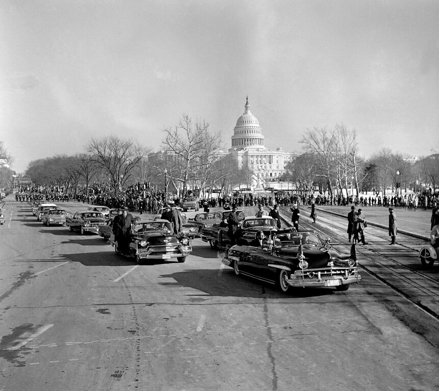 Description of . President John F. Kennedy rides in a black automobile in the traditional inaugural parade in Washington, Jan. 20, 1961. The Capitol is in background. His car is at the intersection of Constitution Ave. left, and Pennsylvania Avenue. (AP Photo)