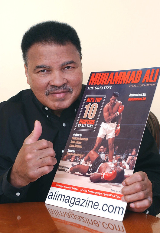 Description of . Boxing legend Muhammad Ali poses with a copy of a new magazine that chronicles his life and career in the ring Monday, March 11, 2002, in Beverly Hills, Calif. The collectible magazine features articles written by former boxing champs and includes paintings, sketches, cartoons and photographs of Ali throughout his career. (AP Photo/Silver Star Media Group, Inc., Rene Macura)