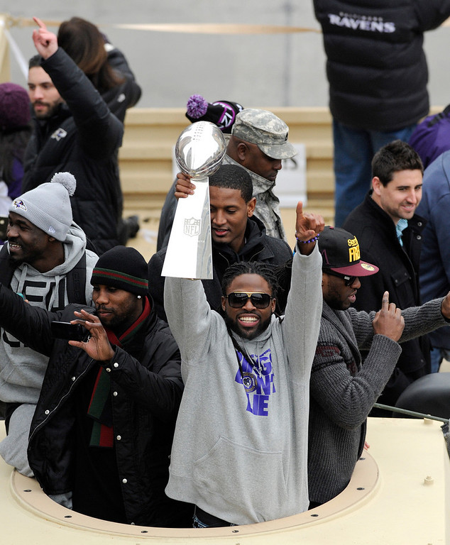 Description of . Baltimore Ravens wide receiver Torrey Smith, center, holds the Vince Lombardi championship trophy during a parade and celebration of the team's  NFL football Super Bowl championship in Baltimore on Tuesday, Feb. 5, 2013. The Ravens defeated the San Francisco 49ers 34-31 on Sunday in New Orleans. (AP Photo/Steve Ruark)