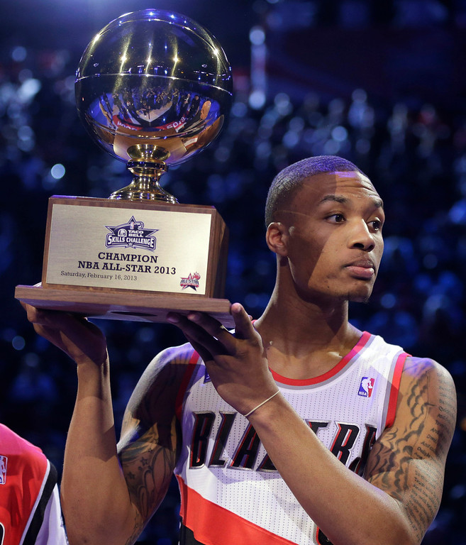 Description of . Damian Lillard of the Portland Trail Blazers raises the trophy after winning the skills challenge during NBA basketball All-Star Saturday Night, Feb. 16, 2013, in Houston. (AP Photo/Eric Gay)
