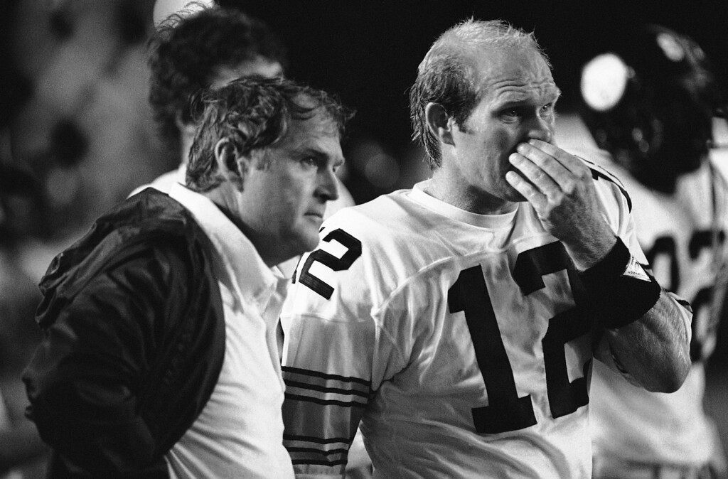 Description of . Pittsburgh Steelers quarterback Terry Bradshaw (12) is flanked by head coach Chuck Noll as the pair watch the Miami Dolphins offense on the field during the second quarter of game in the Orange Bowl Stadium in Miami, Sept. 10, 1981. The Dolphins were leading at the time, and had just intercepted a Bradshaw pass. (AP Photo/Kathy Willens)
