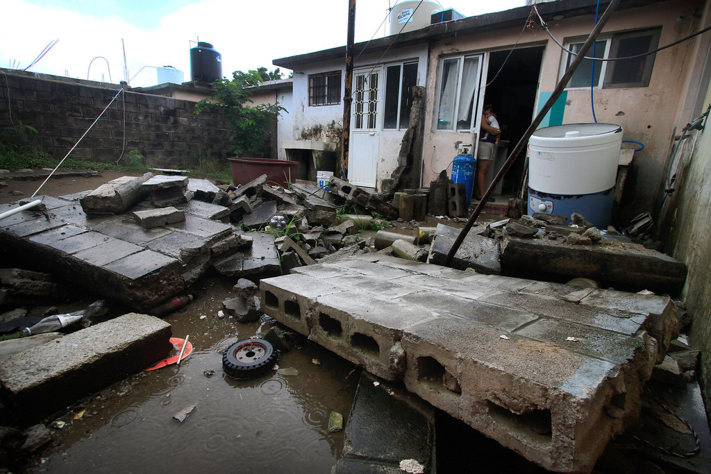 Description of . A woman holds her baby while standing at the door of her damaged house in Veracruz, Mexico, on September 17, 2013 following heavy rains in the country. Mexican authorities scrambled Tuesday to launch an air lift to evacuate tens of thousands of tourists stranded amid floods in the resort of Acapulco following a pair of deadly storms. At least 48 people were killed and thousands evacuated from towns on the Pacific and Gulf of Mexico coasts over the weekend as Tropical Storm Manuel and downgraded Hurricane Ingrid set off landslides and floods that damaged bridges, roads and homes.  KORAL CARBALLO/AFP/Getty Images