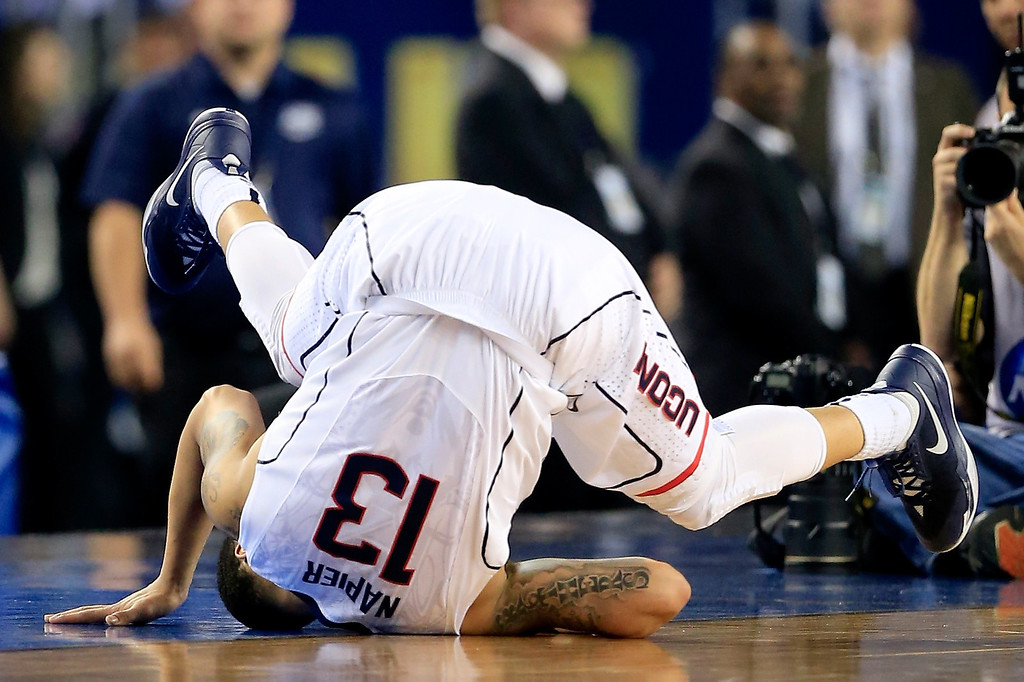 Description of . ARLINGTON, TX - APRIL 07: Shabazz Napier #13 of the Connecticut Huskies falls to the ground during the NCAA Men\'s Final Four Championship against the Kentucky Wildcats at AT&T Stadium on April 7, 2014 in Arlington, Texas.  (Photo by Jamie Squire/Getty Images)