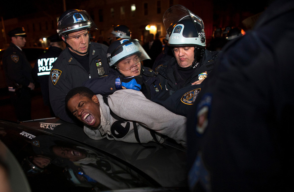 Description of . New York Police Department (NYPD) officers arrest a young man during a protest against the killing of 16-year-old Kimani