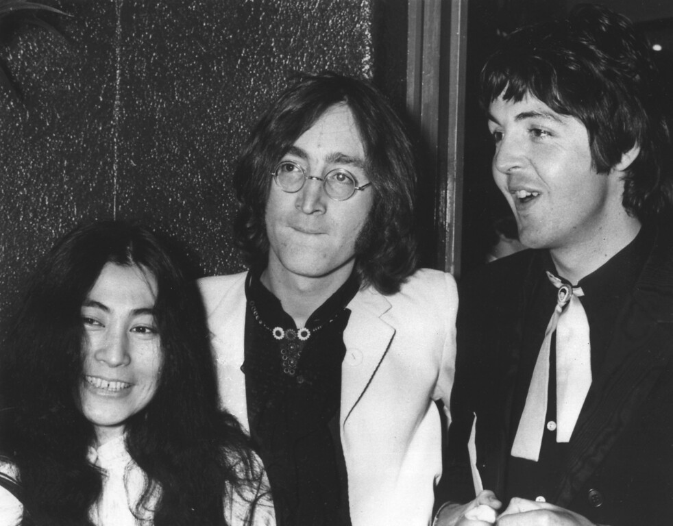 Description of . Beatles John Lennon, center, and Paul McCartney, arrive at the London Pavillion cinema on July 17, 1968 for the premiere of their new animation film