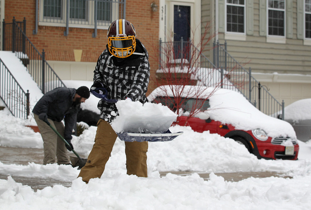 Description of . Local residents shovel snow in front of their houses February 13, 2014 in Alexandria, Virginia. The Washington, DC, area is embracing the biggest sown storm in four years. Most of the metropolitan area has received almost a foot of snow so far.  (Photo by Alex Wong/Getty Images)