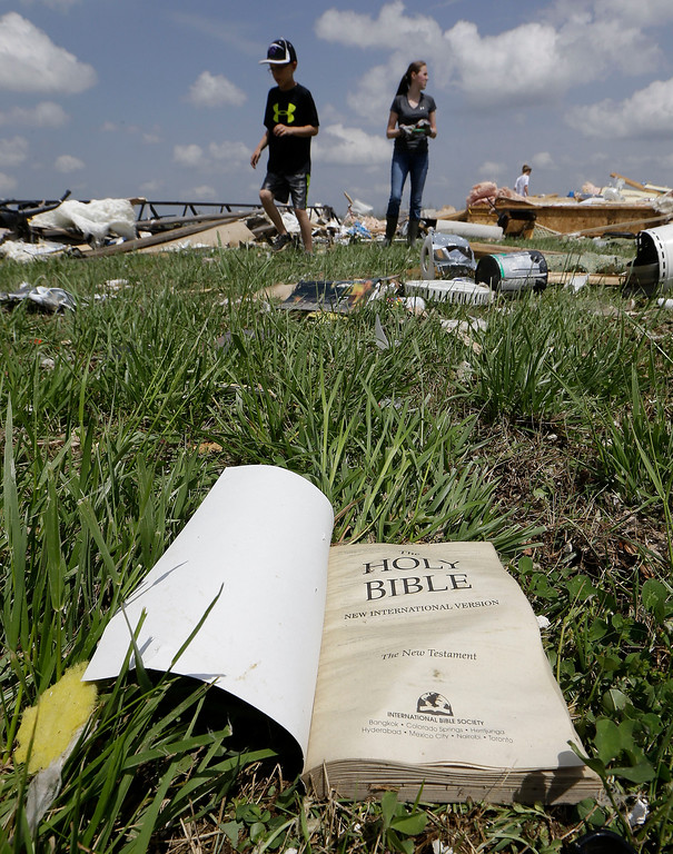 Description of . A Bible lies on the ground as people salvage items from Grace Falls Church Tuesday, April 29, 2014, in Fayetteville, Tenn. The church was destroyed by storms Monday.  A dangerous storm system that spawned a chain of deadly tornadoes over three days flattened homes and businesses, forced frightened residents in more than half a dozen states to take cover and left tens of thousands in the dark Tuesday morning. (AP Photo/Mark Humphrey)