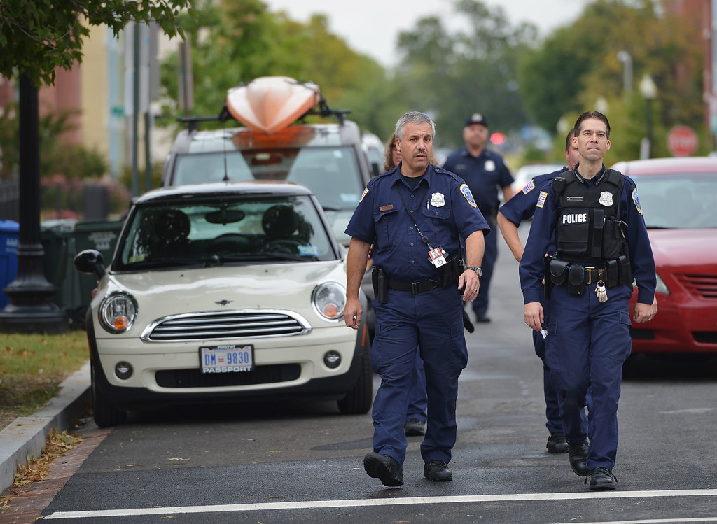Description of . Police walk on a residential street near the Washington Navy Yard on September 16, 2013 in Washington, DC. One gunman has been killed and up to two more may still be at large after a shooting rampage at the US Naval base in Washington on Monday that left