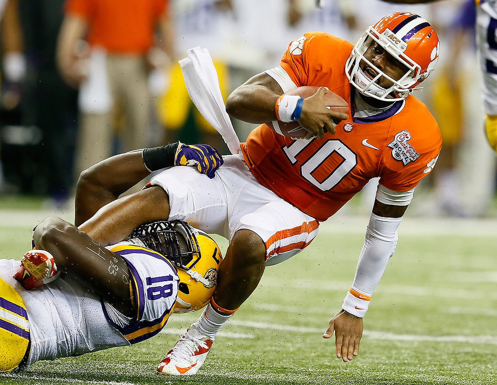 Description of . Bennie Logan #18 of the LSU Tigers tackles Tajh Boyd #10 of the Clemson Tigers during the 2012 Chick-fil-A Bowl at Georgia Dome on December 31, 2012 in Atlanta, Georgia.  (Photo by Kevin C. Cox/Getty Images)