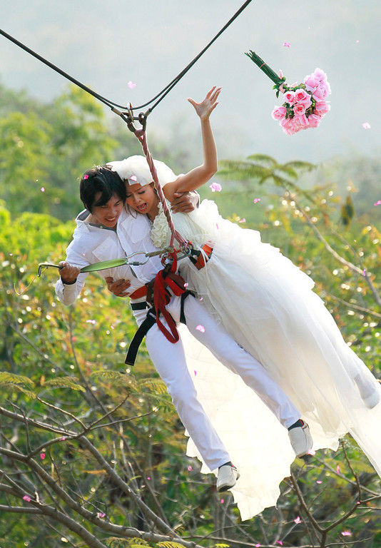 Description of . Sopon Tapoatong, left, and his bride Chutuma Tapoatong swing out on a rappelling rope as part of an adventure themed wedding ceremony in Prachinburi province, Thailand, Wednesday, Feb. 13, 2012, on the eve of Valentine's Day. (AP Photo/Wason Wanichakorn)