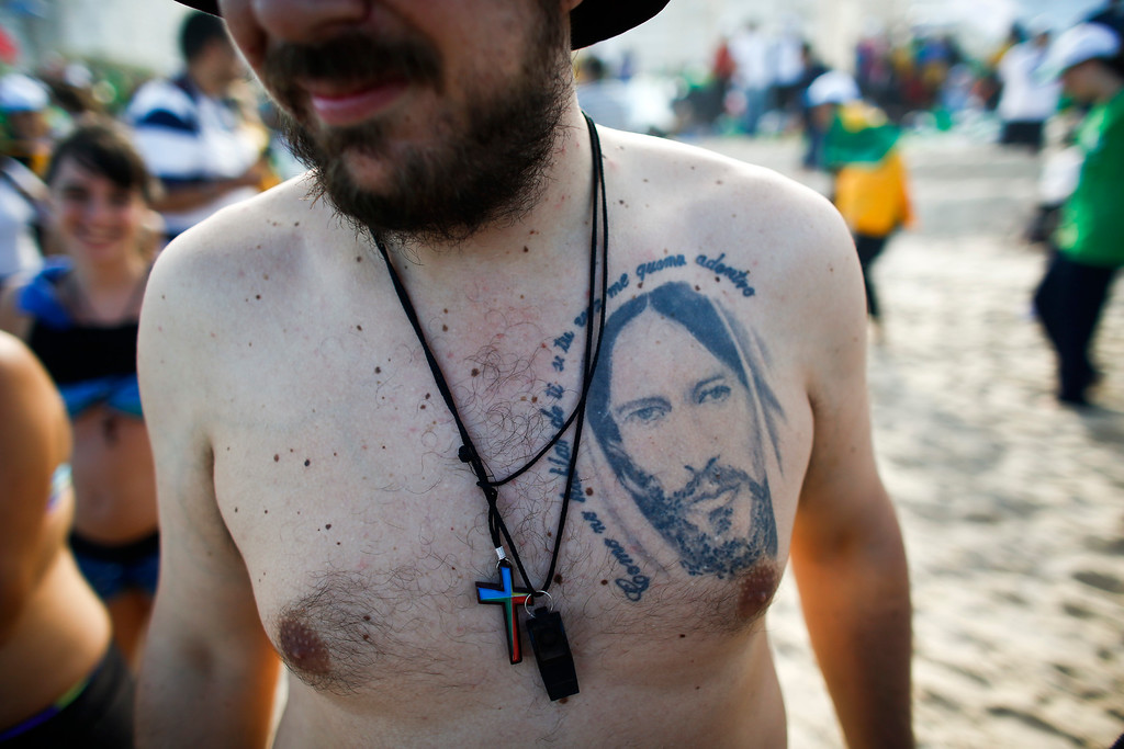 Description of . A pilgrim from Argentina on Copacabana beach has a Jesus tattoo that reads in Spanish