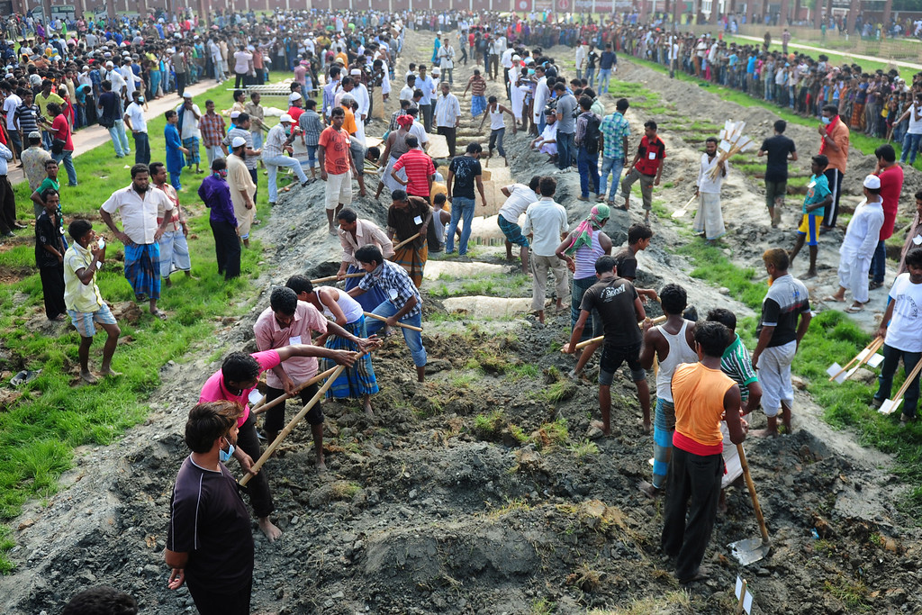 Description of . Bangladeshis bury the remains of garment workers killed in the garment factory collapse at a graveyard in Dhaka on May 1, 2013. AFP PHOTO/Munir uz  ZAMAN/AFP/Getty Images