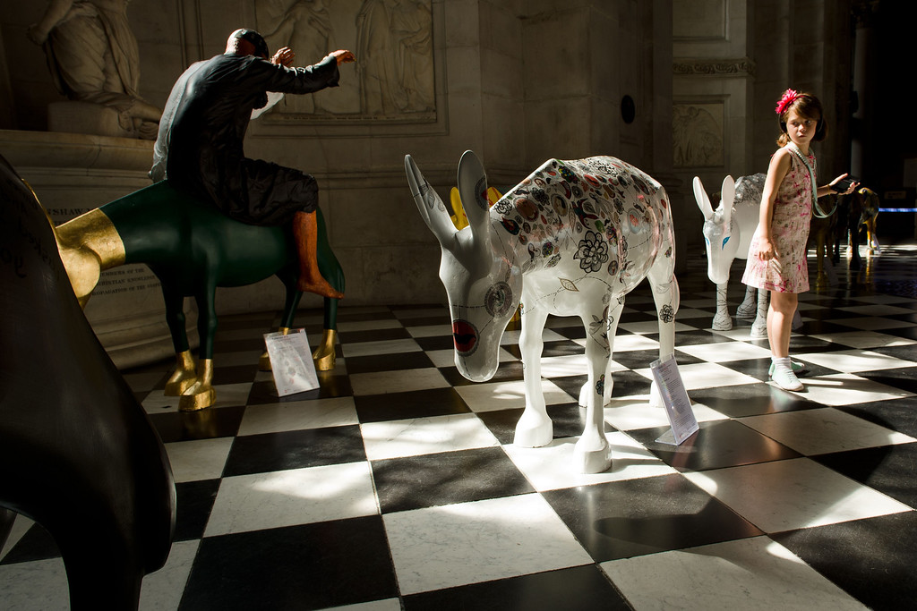 . A girl explores some of the 25 life-size painted donkeys, created by Egyptian and Western artists as they go on display in St Paul\'s Cathedral in London on August 30, 2013.   AFP PHOTO / LEON NEALLEON NEAL/AFP/Getty Images