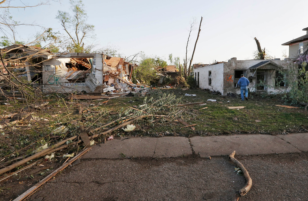 Description of . Bob Hessee checks out property owned by a friend and damaged by a tornado in Baxter Springs, Kan., Monday, April 28, 2014.  A tornado damaged dozens of buildings and injured at least 25 people on Sunday. (AP Photo/Orlin Wagner)