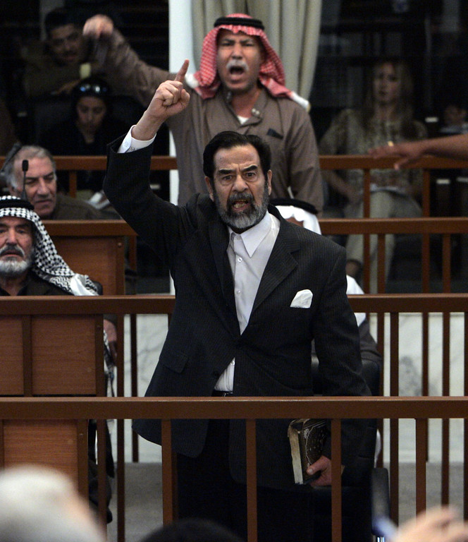 Description of . Former Iraqi President Saddam Hussein, front center, and Barzan Ibrahim al-Tikriti, back center, berate the court during their trial in Baghdad, in this Dec. 5, 2005, file photo. (AP Photo/David Furst, Pool)
