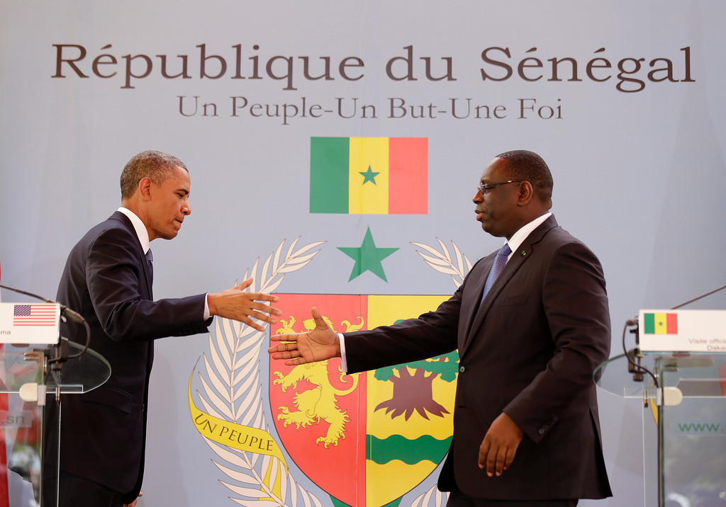 Description of . U.S. President Barack Obama, left, shakes hands with Senegalese President Macky Sall after a joint press conference at the presidential palace in Dakar, Senegal, Thursday, June 27, 2013. President Obama arrived in Senegal Wednesday night to kick off a weeklong trip to Africa, a three-country visit aimed at overcoming disappointment on the continent over the first black U.S. president's lack of personal engagement during his first term. (AP Photo/Rebecca Blackwell)
