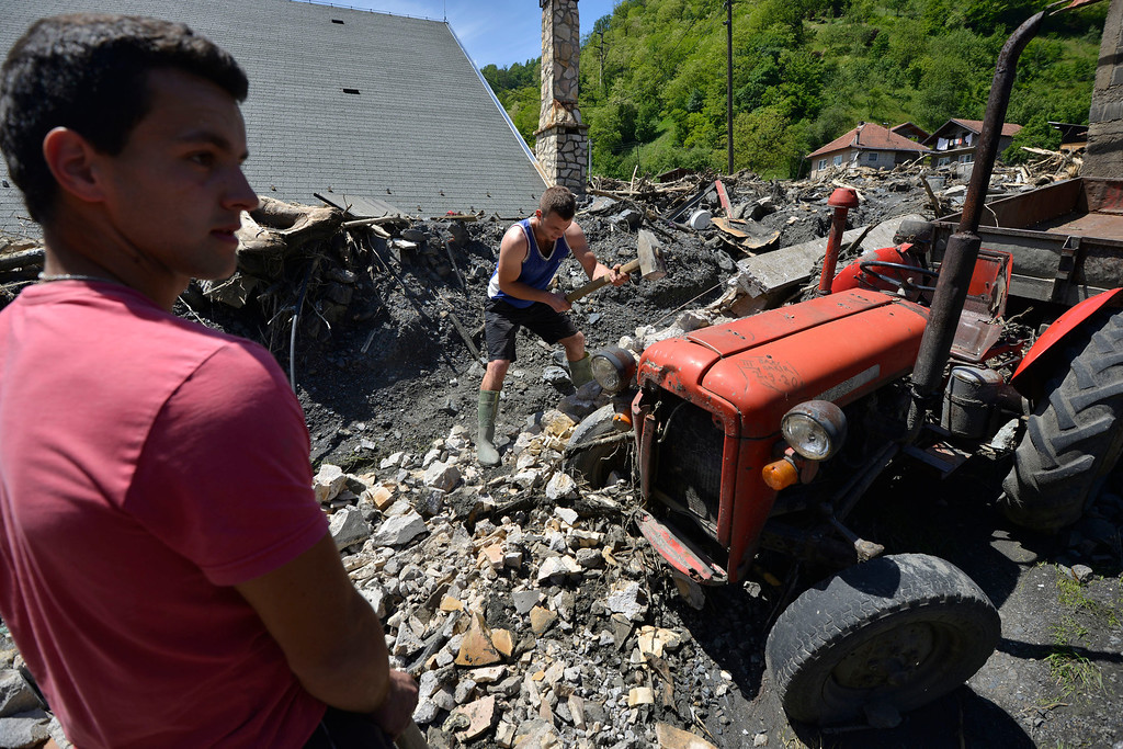 Description of . Volunteers help to clean the village of Topcic Polje, that was damaged by a landslide, near the Bosnian town of Zenica, 90 kilometers north of Sarajevo, on Monday May 19, 2014. At least 35 people have died in Serbia and Bosnia in the five days of flooding caused by unprecedented torrential rain, laying waste to entire towns and villages and sending tens of thousands of people out of their homes, authorities said. (AP Photo/Sulejman Omerbasic)