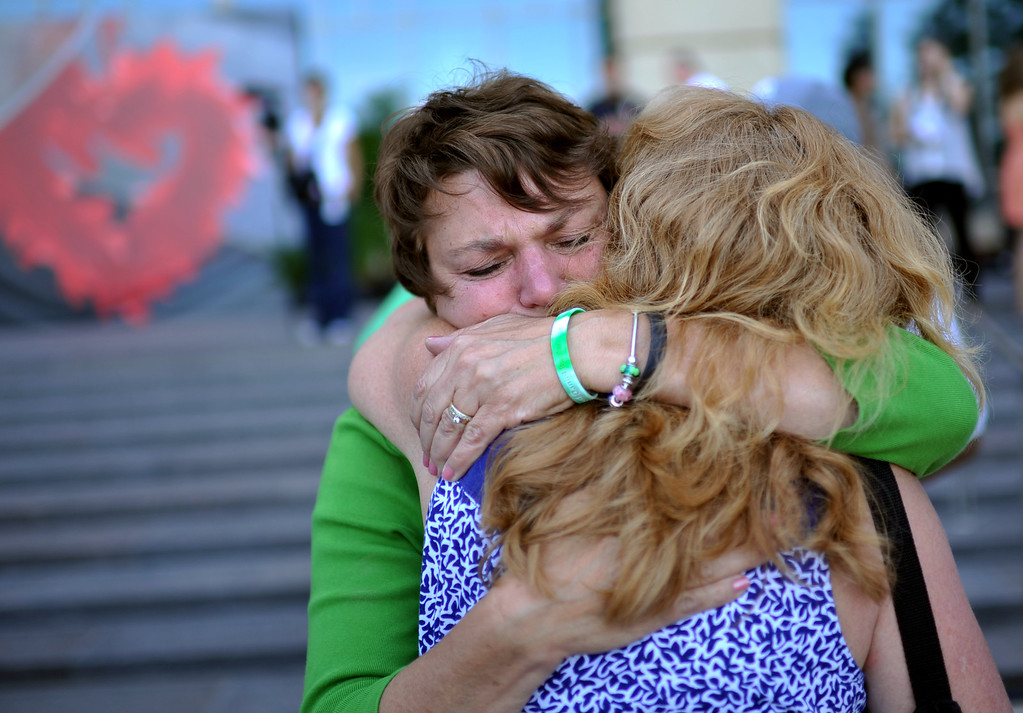 Description of . AURORA, CO. - July 20: Terry Sullivan, mother of 27-year-old Alex who was killed in the Aurora shooting, left, hugs Heidi Bergman Soudani, mother of shooting survivor Farrah Soudani during a day of remembrance at Aurora Municipal Center. Aurora, Colorado. July 20, 2013. People gathered outside the Aurora Municipal Center to mark the first anniversary of the deaths of 12 people and the injury of at least 70 others in a mass shooting that forever changed an entire community. (Photo By Hyoung Chang/The Denver Post)