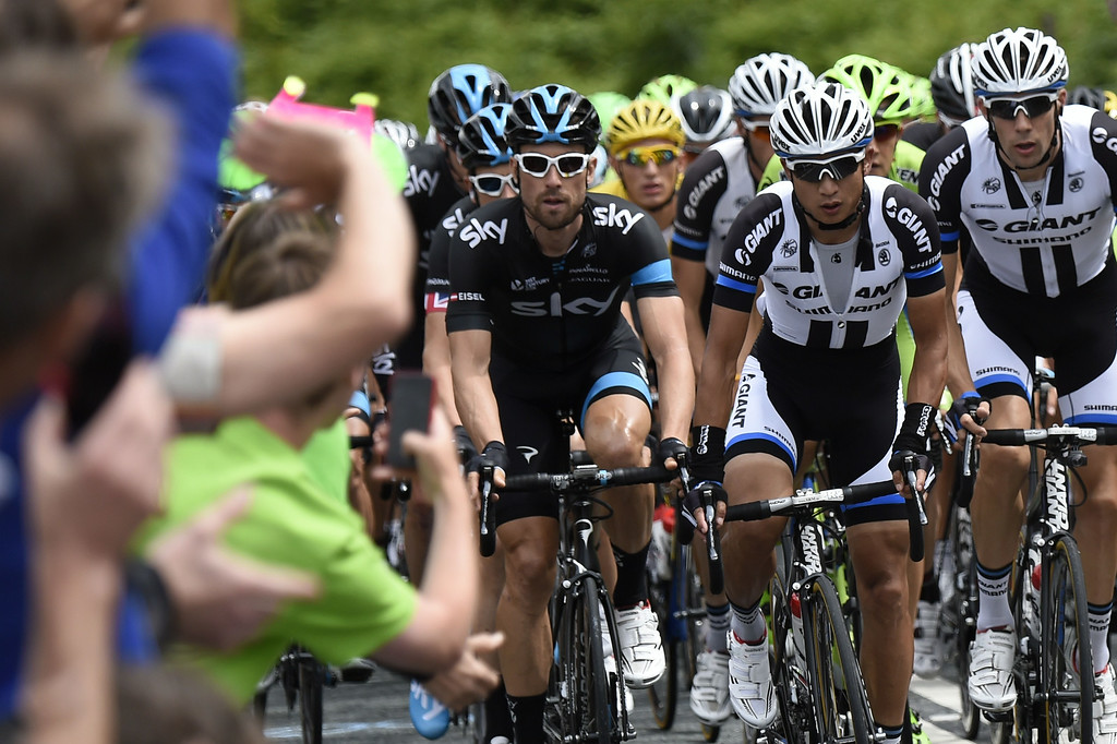 Description of . Austria's Bernhard Eisel (L) and China's Cheng Ji (C) during the 201 km second stage of the 101th edition of the Tour de France cycling race on July 6, 2014 between York and Sheffield, northern England.  AFP PHOTO / ERIC FEFERBERGERIC FEFERBERG/AFP/Getty Images