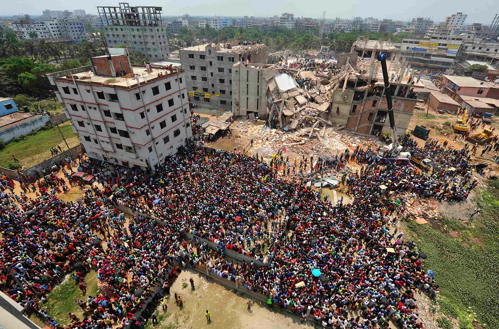 Description of . People gather in front of Rana Plaza building as rescue workers continue their operations, in Savar, 30 km (19 miles) outside Dhaka April 25, 2013. Survivors from the garment factory that collapsed in Bangladesh killing at least 228 people described on Thursday a deafening bang and tremors before the eight-floor building crashed down under them. REUTERS/Stringer