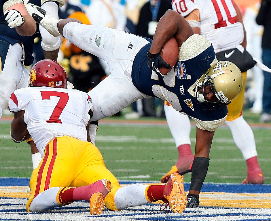 . Georgia Tech running back Davis Sims, right, is tackled by Southern California safety T.J. McDonald during the Sun Bowl NCAA college football game, Monday, Dec. 31, 2012, in El Paso, Texas. Georgia Tech won 21-7. (AP Photo/Mark Lambie)