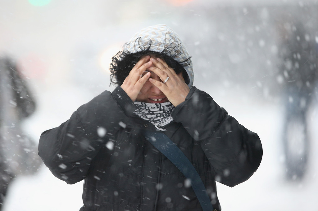 Description of . A woman covers her face while walking through the snow on February 13, 2014 in New York City. Heavy snow and high winds made for a hard commute morning in the city.  (Photo by John Moore/Getty Images)