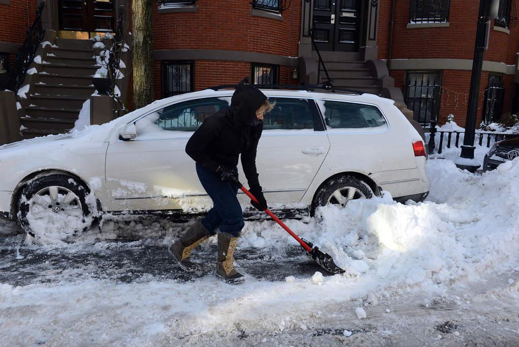 Description of . A woman shovels her car out from snow on East Concord Street in the South End after a two day winter storm January 4, 2014 in Boston, Massachusetts. The storm began mid day Thursday with heavy snows overnight into Friday bringing with it extreme cold. (Photo by Darren McCollester/Getty Images)