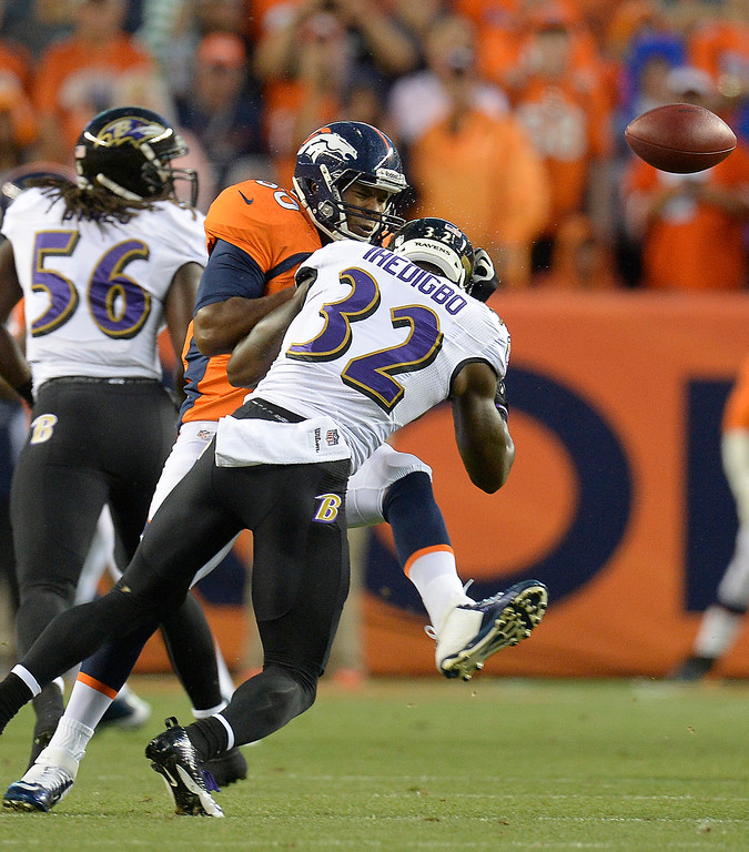 Description of . Denver Broncos tight end Julius Thomas (80) gets hit by Baltimore Ravens strong safety James Ihedigbo (32) as he attempts to catch a pass.   (Photo by John Leyba/The Denver Post)