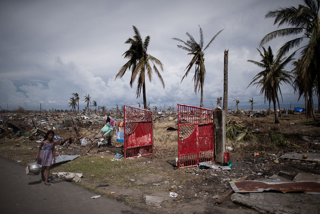 Description of . A typhoon victim (L) walks past land ravaged by Typhoon Haiyan in Tacloban, on the eastern island of Leyte on November 13, 2013 after Super Typhoon Haiyan swept over the Philippines. Five days after Haiyan ripped apart entire coastal communities, the situation in Leyte's provincial capital Tacloban was becoming ever more dire with essential supplies low and increasingly desperate survivors clamoring to leave.   PHILIPPE LOPEZ/AFP/Getty Images