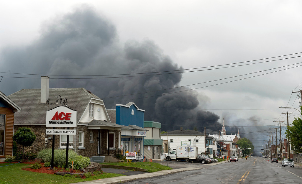 Description of . Smoke rises from railway cars that were carrying crude oil after derailing in downtown Lac Megantic, Quebec, Canada, Saturday, July 6, 2013. The derailment sparked several explosions and forced the evacuation of up to 1,000 people. (AP Photo/The Canadian Press, Paul Chiasson)