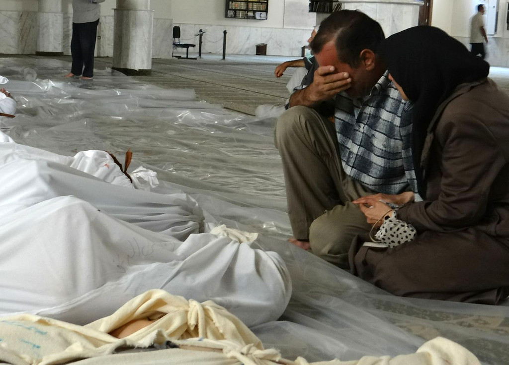 Description of . A handout image released by the Syrian opposition's Shaam News Network shows a Syrian couple mourning in front of bodies wrapped in shrouds ahead of funerals following what Syrian rebels claim to be a toxic gas attack by pro-government forces in eastern Ghouta, on the outskirts of Damascus on August 21, 2013. The allegation of chemical weapons being used in the heavily-populated areas came on the second day of a mission to Syria by UN inspectors, but the claim, which could not be independently verified, was vehemently denied by the Syrian authorities, who said it was intended to hinder the mission of UN chemical weapons inspectors. Ammar al-Arbini/AFP/Getty Images