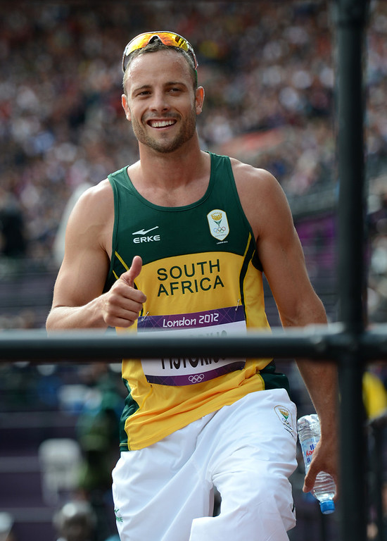 Description of . South Africa's Oscar Pistorius gives a thumbs up before talking to the media in the mix-zone following his Men's 400m heat at the Olympic Stadium for the London 2012 Olympics in London, England on Saturday, Aug. 4, 2012.  (Nhat V. Meyer/Mercury News)