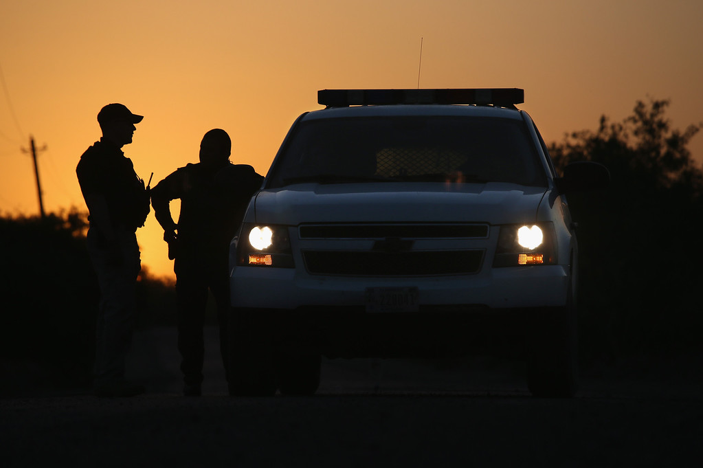 Description of . LA JOYA, TX - APRIL 11:  U.S. Border Patrol agents and a pilot from the U.S. Office of Air and Marine (OAM), stop to talk at sunset on April 11, 2013 in La Joya, Texas. In the last month the Border Patrol\'s Rio Grande Valley sector has seen a spike in the number of immigrants crossing the river from Mexico into Texas. With more apprehensions, they have struggled to deal with overcrowding while undocumented immigrants are processed for deportation. According to the Border Patrol, undocumented immigrant crossings have increased more than 50 percent in Texas\' Rio Grande Valley sector in the last year. Border Patrol agents say they have also seen an additional surge in immigrant traffic since immigration reform negotiations began this year in Washington D.C. Proposed reforms could provide a path to citizenship for many of the estimated 11 million undocumented workers living in the United States.  (Photo by John Moore/Getty Images)